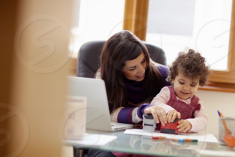 multitasking; child; business; businesswoman; mom; woman; teleworking; 1-2; 2-3; 30s; baby; busy; career; children; computer; corporate; daughter; desk; family; fun; game; girl; happy; hispanic; home; house; indoors; job; laptop; laughing; leisure; mother; motherhood; multi-tasking; occupation; paperwork; pc; people; playing; preschooler; sitting; smiling; stamp; task; technology; together; togetherness; working; years; young photo