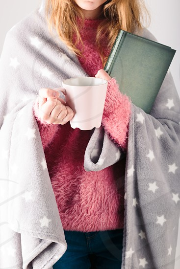 Enjoying the drinking coffee and reading a book. Young girl holding book and cup of coffee going to relax at home photo