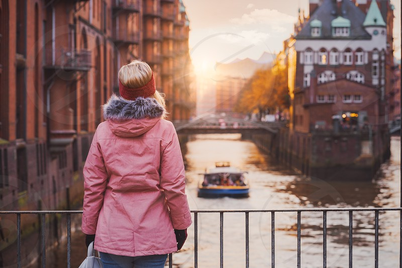 Adult woman tourist enjoying golden sunset light over the Elbe river with pleasure tour boat. Speicherstadt historical warehouse district of Hamburg Germany Europe. photo