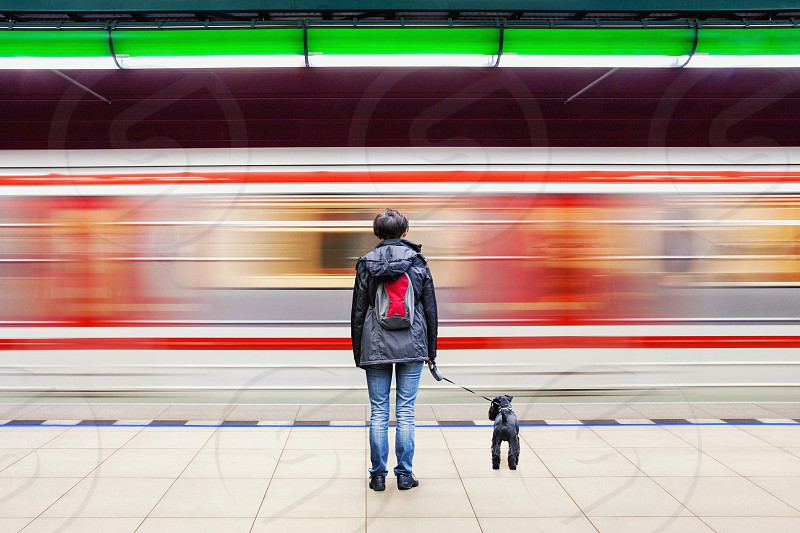 Woman and dog at subway station with moving train in background photo