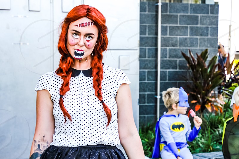 young woman in Halloween costume face paint little superhero eating a treat in the background photo