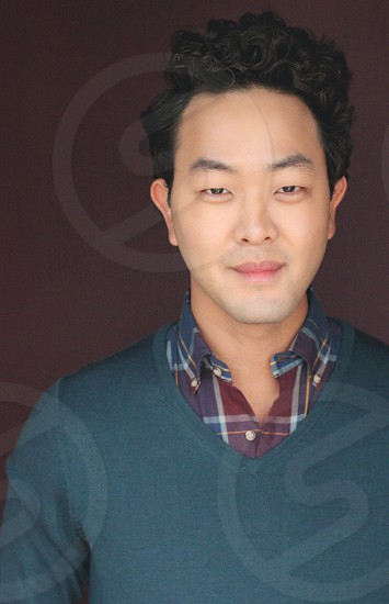 man in gray sweater and black burgundy and gray plaid shirt photo