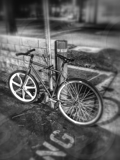 grayscale photo of focused image of a rigid bike locked on a pole beside a half wall made of hollow blocks photo