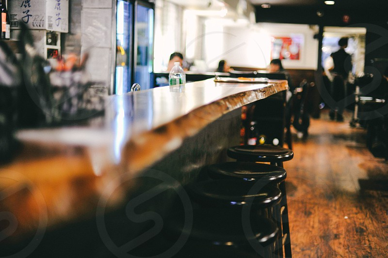 brown wooden bar counter beside black wooden stool photo