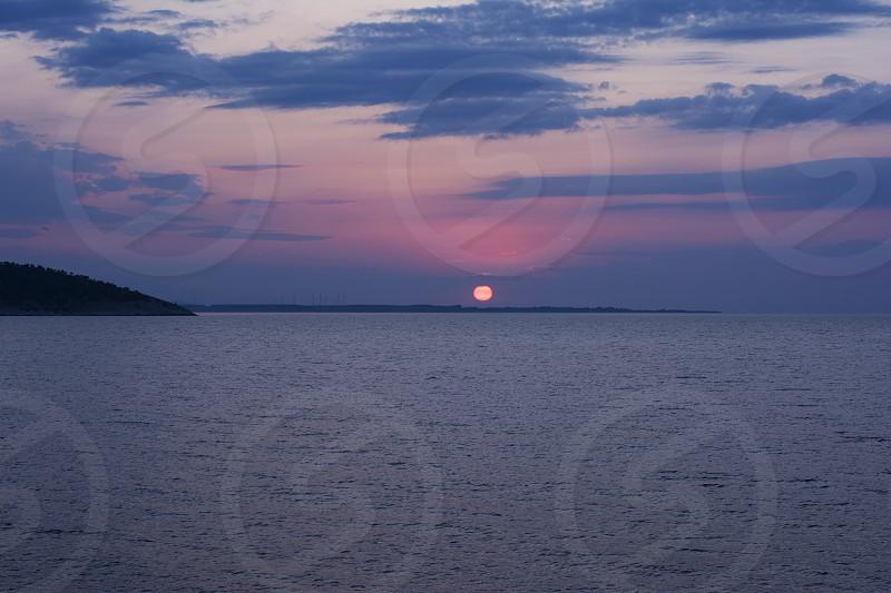 Sun rises above the sea level photo