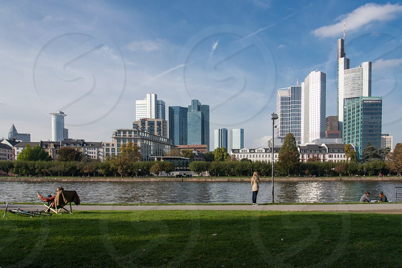 FIGURES IN GREEN GRASS BODY OF WATER NEAR CITY SCAPE photo
