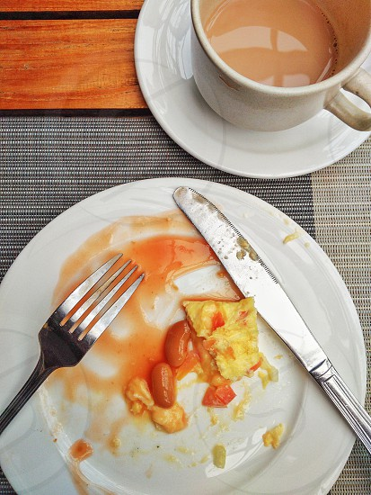Top view of unfinished omelette baked beans cup of coffee and eating utensils on tabletop. photo