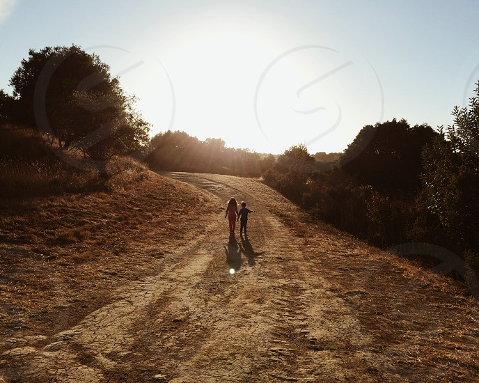 girl and boy walking and holding hands photo