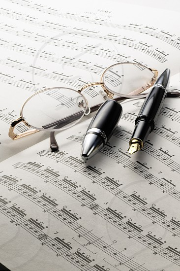 music charts with glasses and pen on top photo