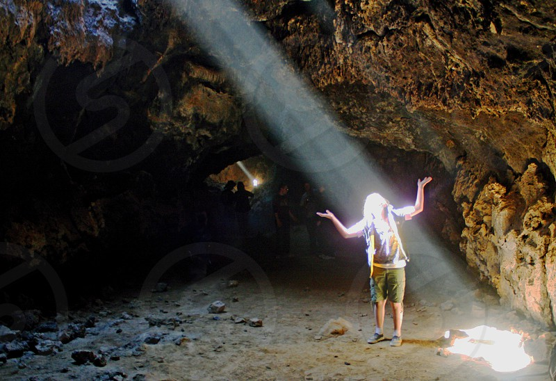 A girl stands in a cave lifting up her arms to touch the beam of light streaming down on her. photo