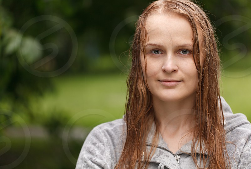Portrait of a girl looking to the photographer in the park after rain with copyspace on left side. photo