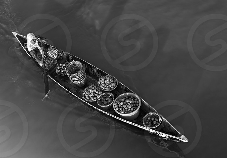 person with baskets sailing on body of water in greyscale photography photo