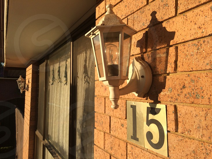 white metal outdoor wall lamp on brown brick wall photo