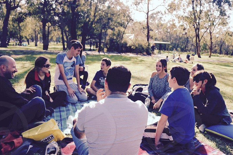 group of people sitting around in a circle conversing happily to each other in the middle of park photo