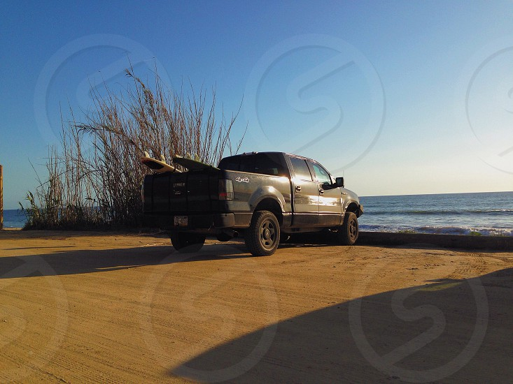 grey 4x4 truck parked at beach  photo