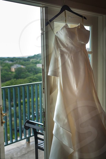 white wedding dress hanging in front of sliding glass door photo