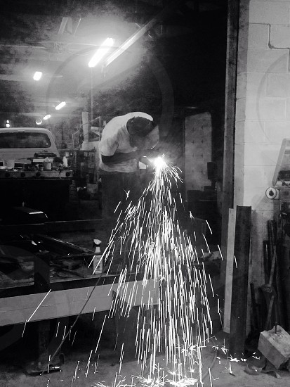 grayscale photo of person welding frame photo