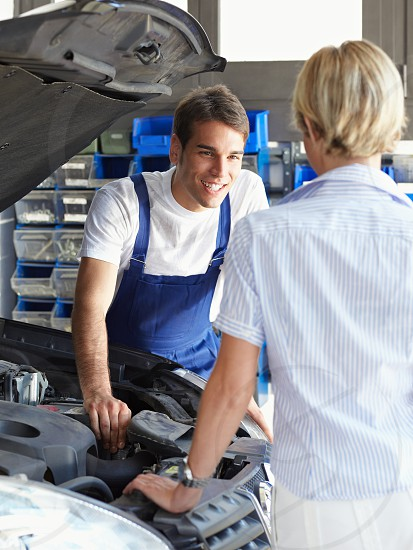 mechanic; client; woman; man; car; auto repair shop; engine; smiling; happy; people; male; female; Caucasian; young; adult; young man; young woman; mid adult; 30s; 20s; front view; happiness; confidence; car owner; looking; repairing; showing; leaning; standing; working; indoors; garage; manual worker; occupation; transportation; transport; vehicle; open; bonnet; hood; auto; automobile; motor vehicle; broken car; repair; car repair; fixing; expertise; skill; courtesy photo