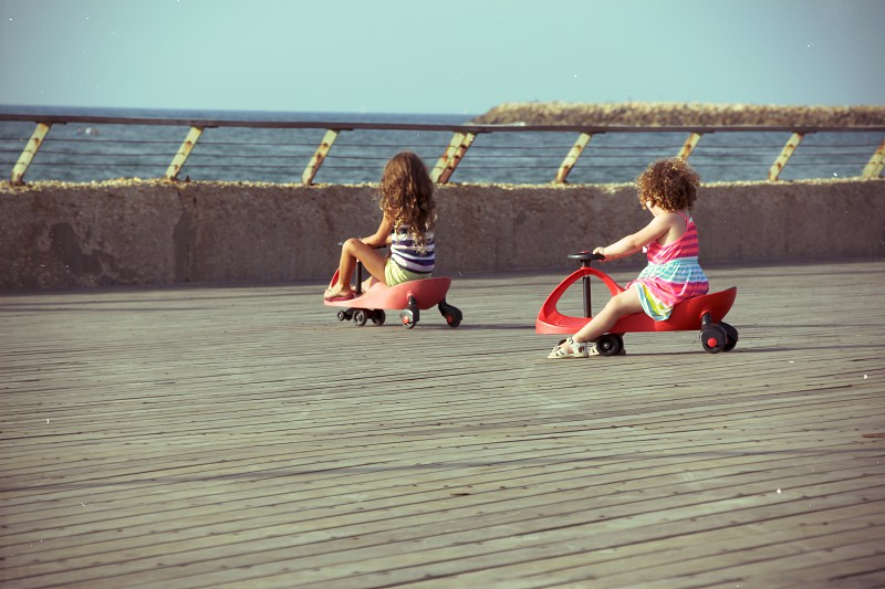 Two little girls riding on toy car (Swing Car \ Bimba) on the jetty by the sea. photo