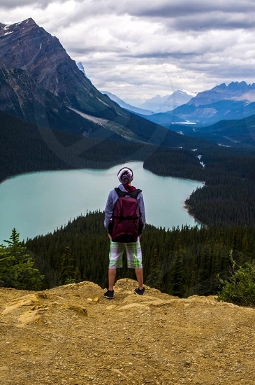 man wearing red backpack standing while facing water body surrounded by mountain ranges photo