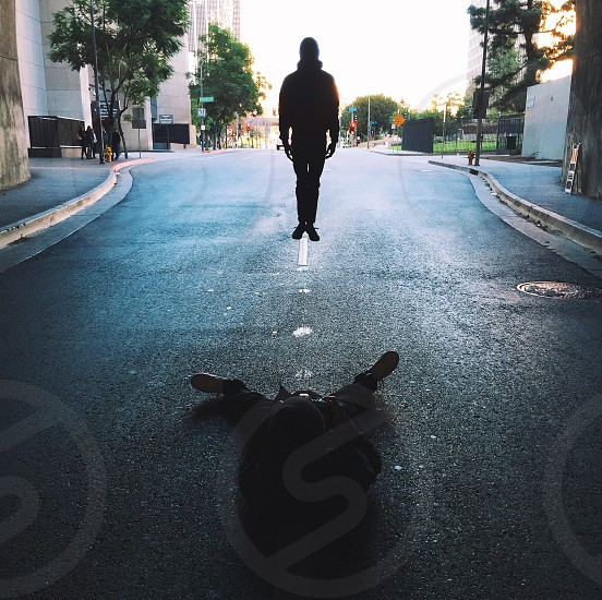 silhouette of a person lying on grey concrete pavement photo