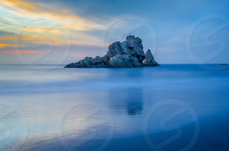 grey rocky islet in blue body of water under blue cloudy sky photo