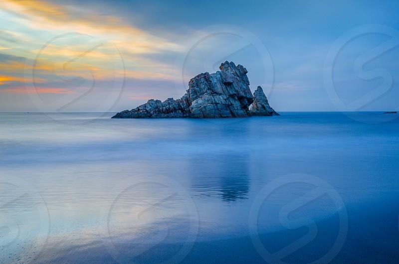 grey rocky islet in blue body of water under blue cloudy sky photo
