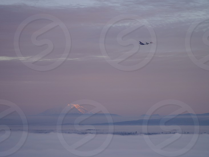 Plane flying with Mt St Helens in background at sunrise.  photo