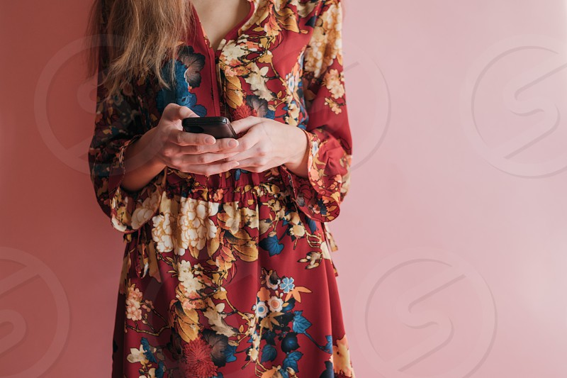 woman using mobile phone at pink background photo