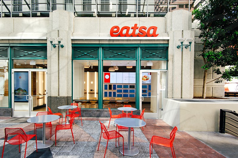 eatsa stall signboard above glass sliding door with metal round dining sets placed outside at daytime photo