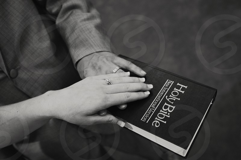 two people touching holy bible photo