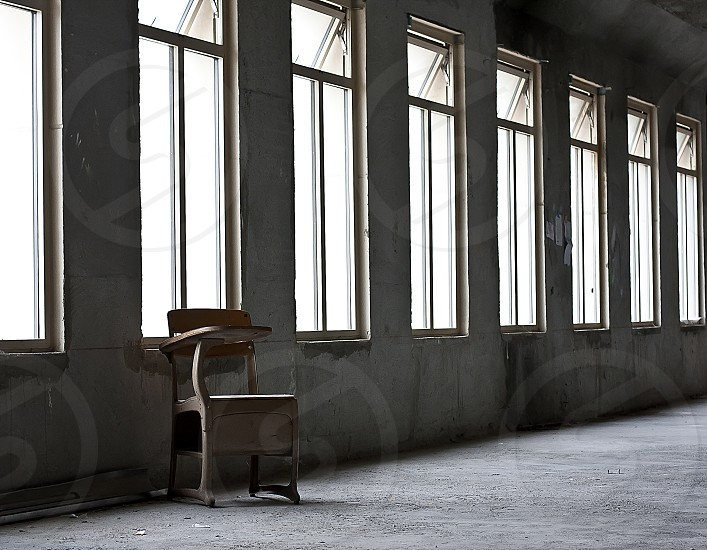 Metal school chair and desk combo sitting alone in an empty abandoned room lined with windows. photo