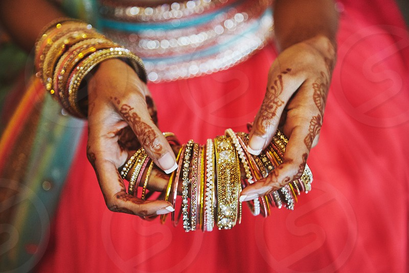 Indian bride hand with henna tattoo art (mehndi) holding bunch of bangles (bracelets) with colorful red sari lehenga traiditional dress on the Indian wedding day. photo