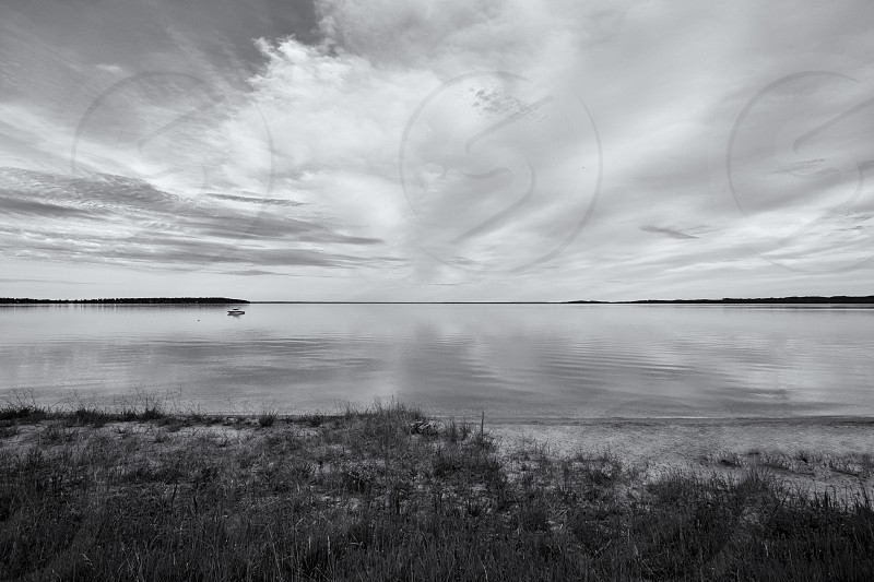 A black and white landscape of a lake with a boat. photo