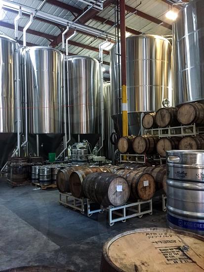 wine barrel arrange on trolley frame with tanks beside photo