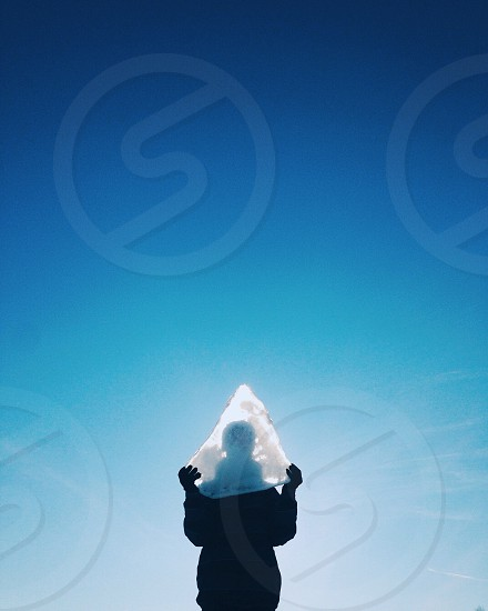 person silhouette holding a piece of pointed ice under a blue sky photo
