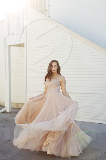 Bride in light pink wedding dress twirls and spins in a circle outside in natural lighting photo