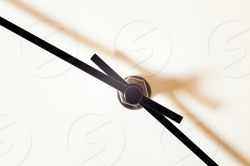 Closeup view of a simple wall watch details of minute and hour hands on white background.  photo