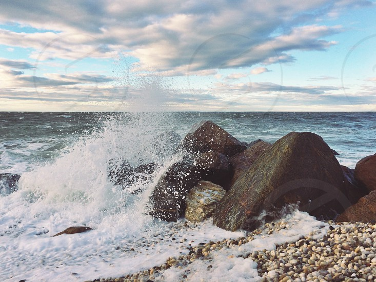 sea waves crashing on stone under cumulus clouds during golden hour photo
