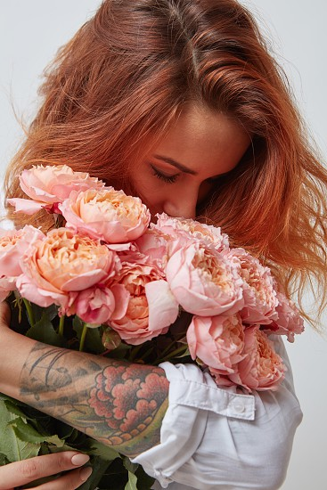 pretty red-haired girl with a tattoo on her arm holding and smell a bouquet of pink roses valentine's day mother's day photo