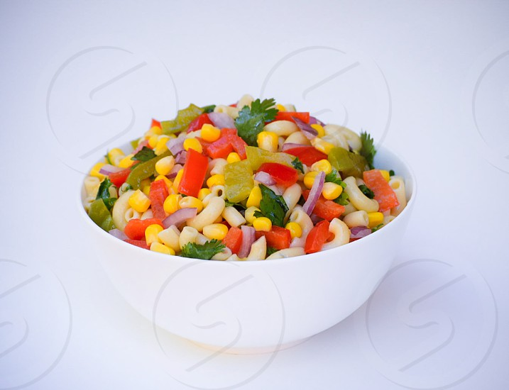 elbow pasta and vegetable salad in white ceramic bowl photo