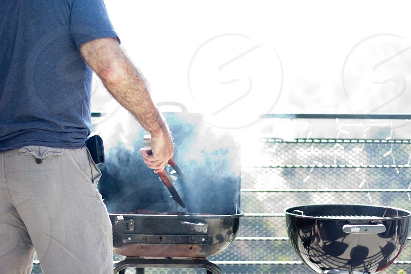 men wearing blue t shirt holding thongs in front of gas grill photo