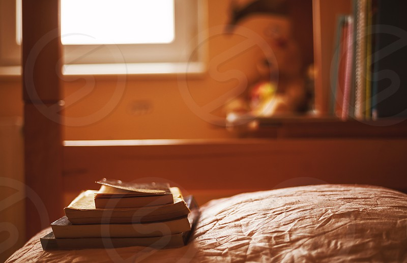 Some books on the bed calm ambiance of teenager's room.  photo