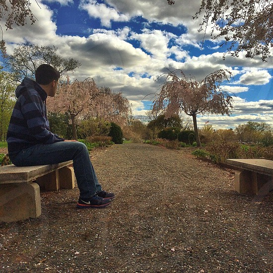 man in blue and black striped hoodie and blue denim jeans sitting on bench photo