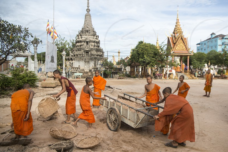 young monks wort at a construction for a new building at the Wat Kampong Thom Temple in the city of Kampong Thom of Cambodia.  Cambodia Kampong Thom November 2017 photo
