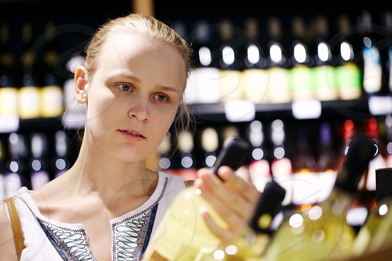 Woman shopping for wine or other alcohol in a bottle store standing in front of shelves full of bottles with a serious expression as she tries to make up her mind photo