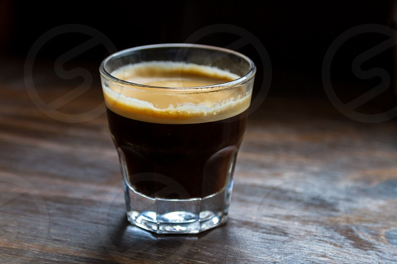 coffee : a short coffee served in a glass on a wooden table.  PS : no need for a model release. photo