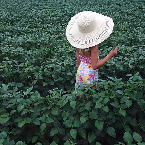 girl wearing white sun hat on green plains photo