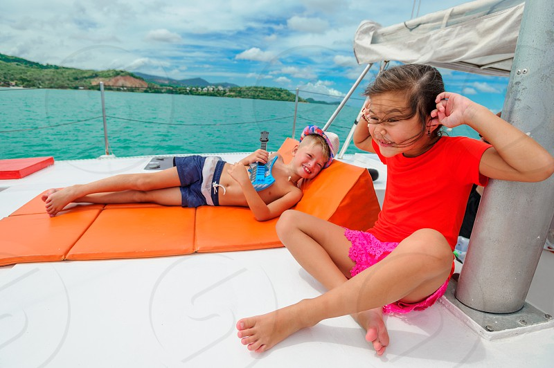 Cute kids on a boat trip. Boy is playing a toy guitar for his beautiful girlfriend photo
