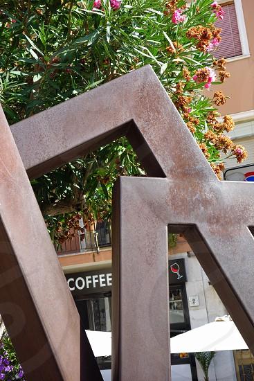 Coffee shop sign seen through modern angular metal sculpture... photo